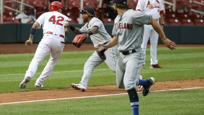 The St. Louis Cardinals' Yadier Molina, left, is tagged out by Indians first baseman Carlos Santana during the 12th inning Saturday.