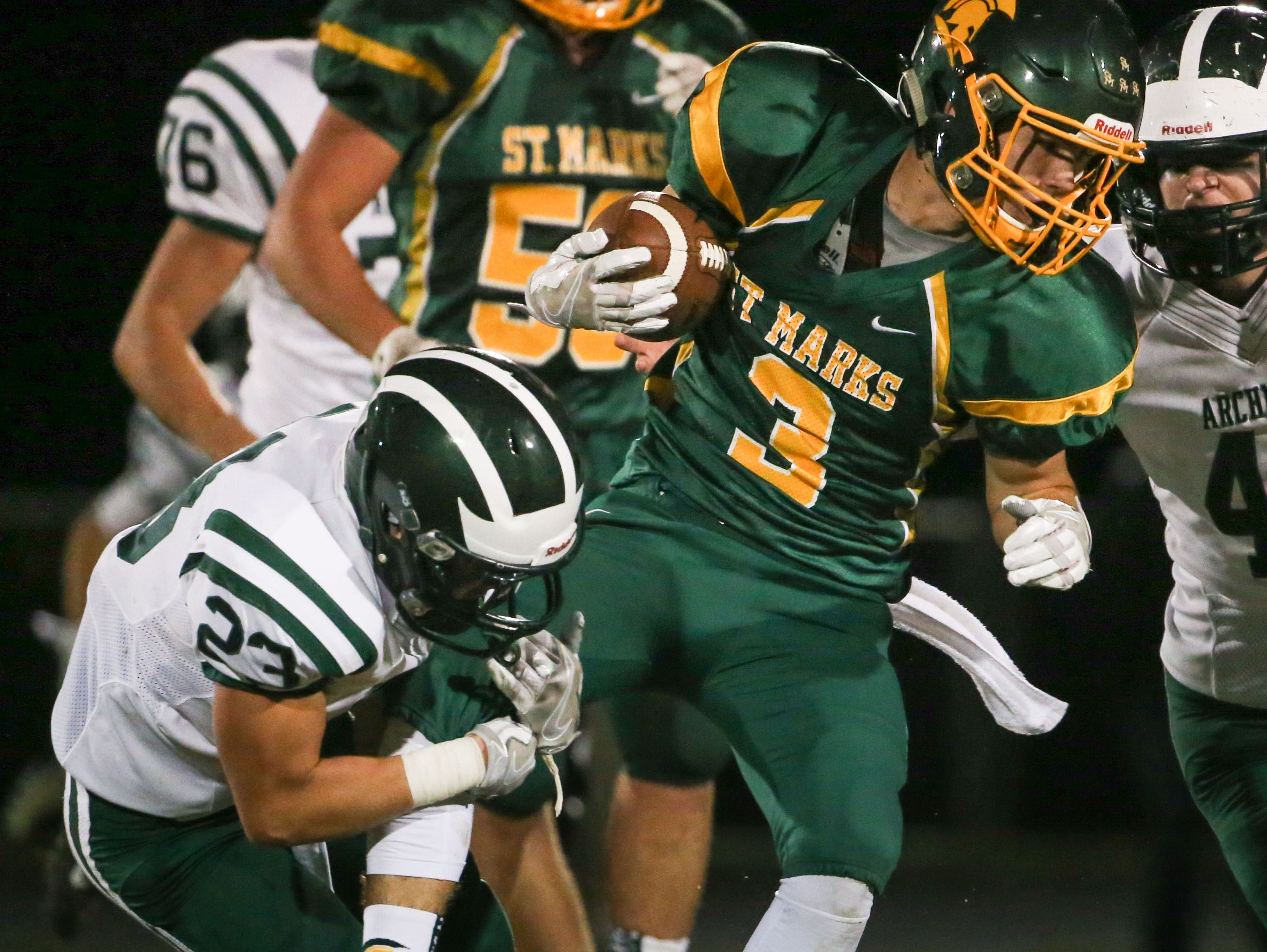 St. Mark's running back Maxwell Palmer is tied up by Archmere defensive back Patrick McVey in the second quarter of their game at St. Mark's Friday.