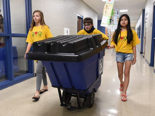 Hackler Intermediate School students Victoria Glenn, from left, Kellis Wilson and Emily Van head to a classroom on Monday to recycle paper. The school is one of only six schools in Arkansas to win the Arkansas Green Schools Challenge. Students have recycled since the school opened in 2010.