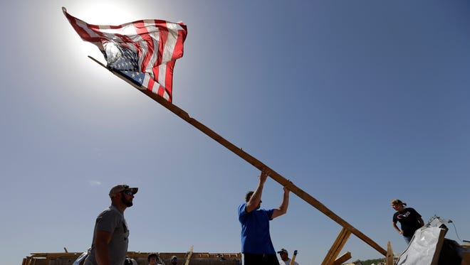 Justin Shaw, left, helps Nick Conway erect a  flag pole at his home that was destroyed by a tornado on April 28 in Vilonia, Ark.