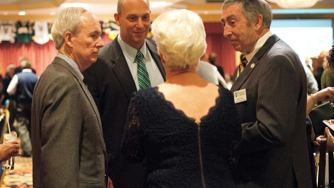 Jeff Schulman, background, is flanked by UVM President Tom Sullivan, left, and athletic director Bob Corran, at the school's athletic hall of fame banquet last year. Schulman is the lone finalist in the running to replace Corran, who is retiring June 30.