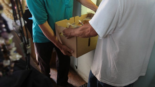 FISH Food Bank volunteers carry a box of food.