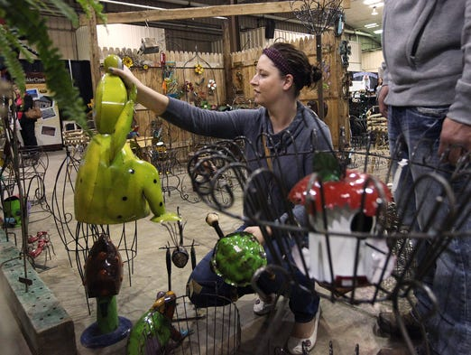 Emily Gislason picks out a metal frog at the Rustic Designs and More booth during The Sioux Falls Lawn and Garden Show at W.H. Lyon Fairgrounds on Sunday, March 30, 2014.