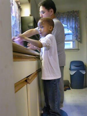 A foster father and son wash dishes.