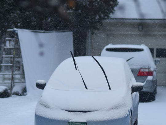Snow covers a car on Brewer Parkway in South Burlington