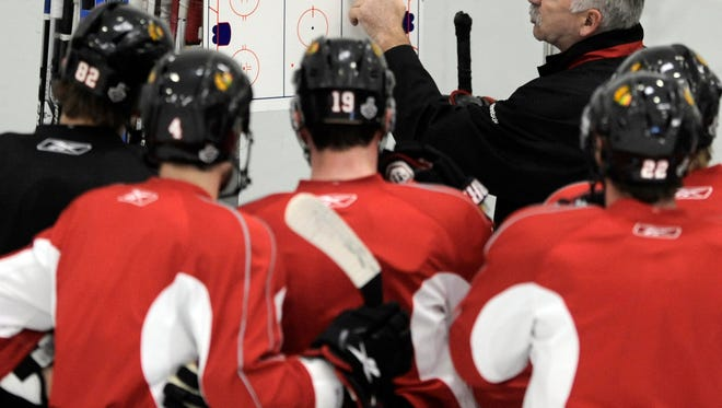Chicago Blackhawks head coach Joel Quenneville talks to his players during hockey practice at Johnny's Ice House West in Chicago.
