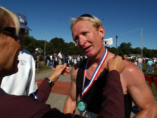 In this file photos from September 2009, Mike Slinskey gets a medal after winning the Dutchess County Classic half-marathon.