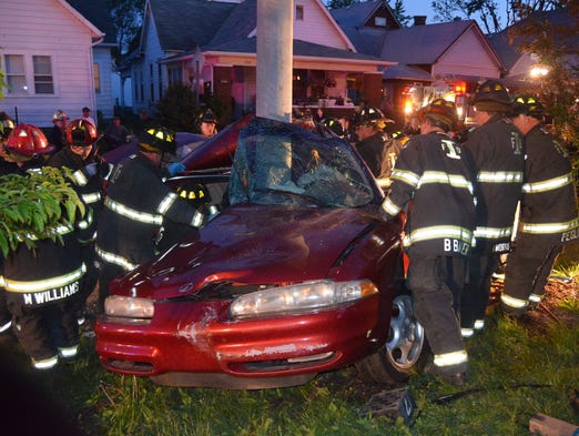IFD rescue personnel work to extricate Ithe 17 year-old white male from the wreckage of his   red Oldsmobile Intrigue that collided with a utility pole at 727 E. Morris Street, at 9 p.m. Sunday May 18, 2014. It took fire rescue companies 15 minutes to extricate the victim and he was transported to Eskenazi Hospital.