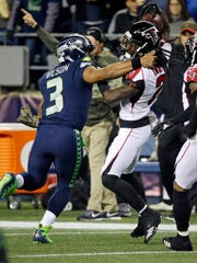Russell Wilson tackles Desmond Trufant throwing an interception on the Seahawks' first possession on Monday in Seattle.