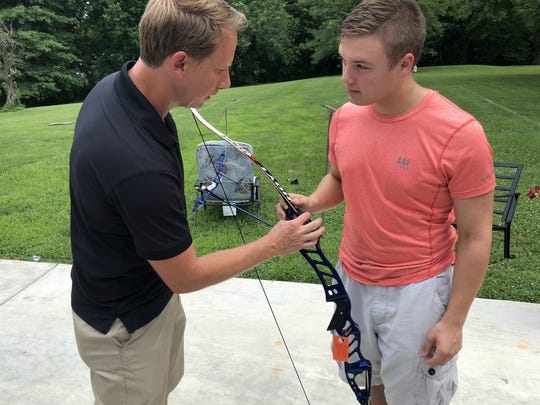 Doug Denton, left, an engineer with Hoyt Archery, talks to Dalton Hinkle about the Hoyt Formula Faktor bow that Hinkle won for finishing first in the NASP national championships in May. Denton, a native of Robards, is the bow's designer and hand-delivered it to the Hinkle's home on Tuesday.
