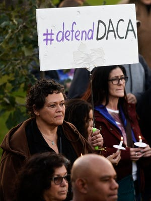 Dr. Dawn Dale holds a sign in support of the DACA program. Sioux Falls residents gathered Tuesday night for a candle light vigil to protest the Trump administration's announcement that it would be ending the Deferred Action for Childhood Arrivals program. More than 500 undocumented immigrants have been approved to work in South Dakota through the DACA program since 2012.