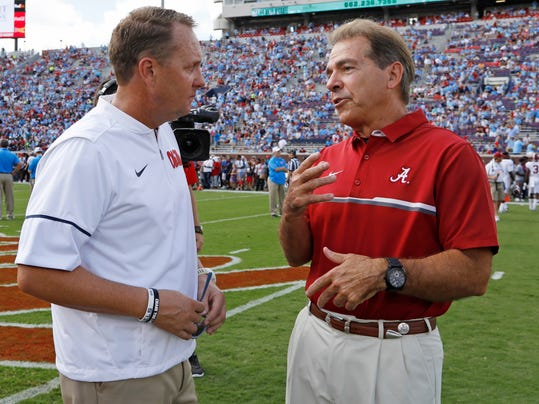 """FILE - In this Sept. 17, 2016, file photo, Mississippi coach Hugh Freeze, left, and Alabama coach Nick Saban chat before an NCAA college football game in Oxford, Miss. Southeastern Conference coaches unanimously agree on one topic at the league's spring meetings this week: They disapprove of NCAA recruiting reforms passed in May. """"I think it's reckless, really,"""" Freeze said. Added Saban: """"Sometimes we take a sledgehammer to kill a fly and it has some unintended consequences, which we may see here sometime in the future."""" (AP Photo/Rogelio V. Solis, File)"""