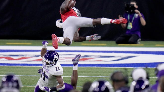 Ohio State running back Trey Sermon, top, is sent flying by Northwestern defensive back A.J. Hampton (11) during the first half of the Big Ten championship NCAA college football game, Saturday, Dec. 19, 2020, in Indianapolis.