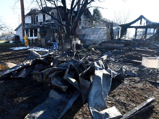 Investigators sift through the rubble after a fire