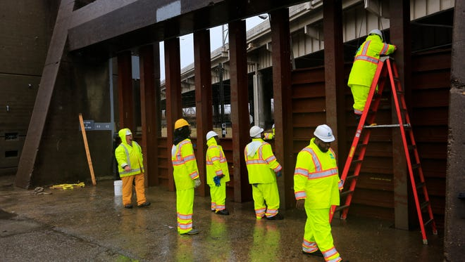 MSD workers install flood gates on 10th Street in Louisville. Feb. 24, 2108