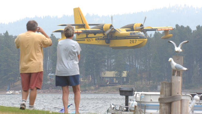 A firefighting airplane comes in low to scoop water from Seeley Lake just off shore from the town of Seeley Lake,Mont., as the Jocko Lakes fire burns nearby,  Tuesday, Aug. 7, 2007.