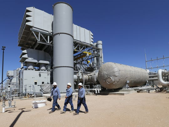 Workers walk past one of four generating units at the