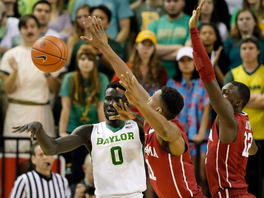 Baylor forward Jo Lual-Acuil Jr. (0) of Australia passes the ball under pressure from Oklahoma's Dante Buford (21) and Khadeem Lattin (12) in the first half of an NCAA college basketball game, Tuesday, Feb. 21, 2017, in Waco, Texas. (AP Photo/Tony Gutierrez)