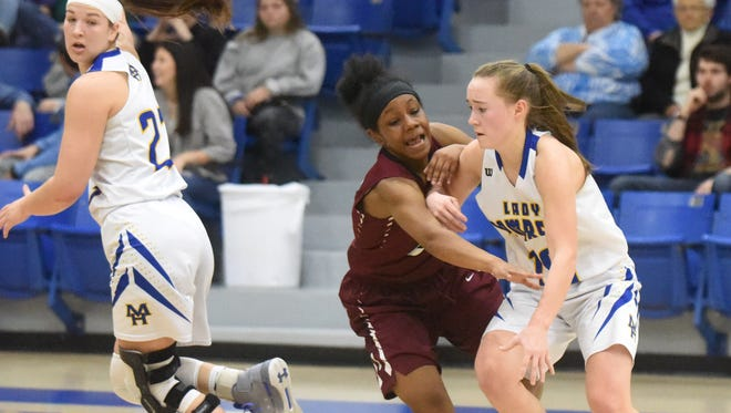 Mountain Home's Payton Huskey is defended by Pine Bluff's Breanna Gray as Maly Tabor rolls off a screen during the Lady Bombers' 47-32 victory over the Fillies on Saturday at The Hangar.