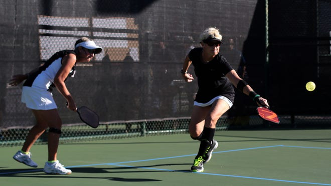 Mary Barsaleau returns a backhand as Karen Bush looks on in this file photo.