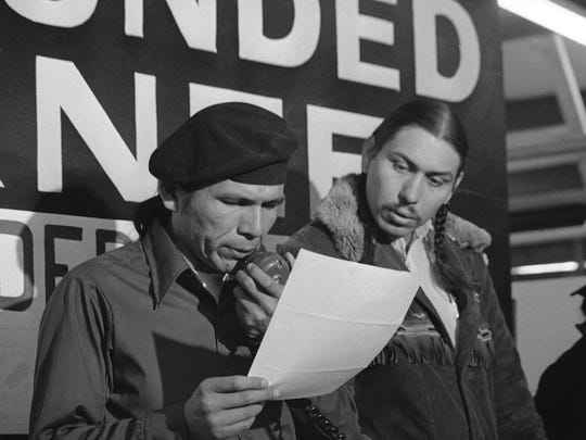 In this March 18, 1973, file photo taken in Wounded Knee, S.D., American Indian Movement leader Dennis Banks, left, reads an offer by U.S. government seeking to effect an end to the Native American takeover of Wounded Knee. Looking on is AIM leader Carter Camp. The family of Banks said he died Sunday, Oct. 29, at the age of 80.