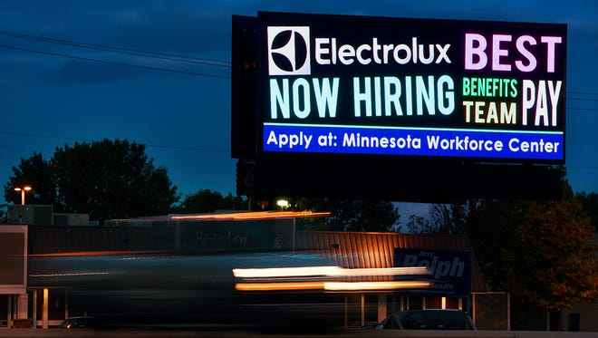 Cars stream past a lighted billboard flashing multiple businesses looking for employees on Thursday, Aug. 25, along Minnesota Highway 23 in St. Cloud.
