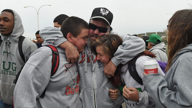 Kelly Young hugs his children Logan, left, and Brianna an they come out of the Hug high campus where an officer involved shooting occurred on Dec. 7 2016.