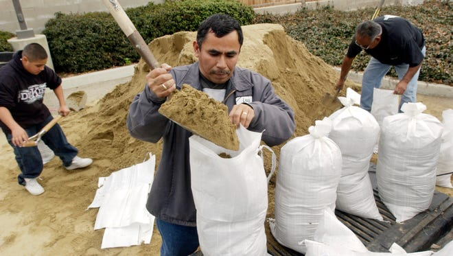 Christopher Sedillo, 13, left; his grandfather, Marcos Lopez; and Samuel Mosqueda fill sandbags in 2008 at Visalia Fire Station 54.