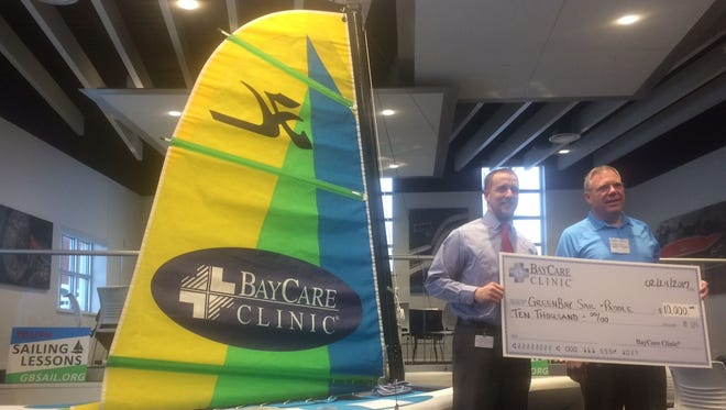 Mike Schmidt, left, business development director for BayCare Clinic, presents a $10,000 check from the Green Bay medical provider to John Kelly of Green Bay Sail & Paddle at an event for the nonprofit at The Automobile Gallery in downtown Green Bay on Friday night, Feb. 24, 2017. The donation was used to purchase a Hobie Wave sailboat that Green Bay Sail & Paddle will use in its classes this summer.
