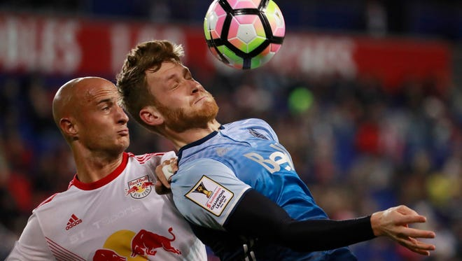 Vancouver Whitecaps forward Kyle Greig, right, tries to control the ball as New York Red Bulls defender Aurelien Collin defends during the second half of a CONCACAF Champions League quarterfinal soccer match, Wednesday, Feb. 22, 2017, in Harrison, N.J. The teams tied 1-1. (AP Photo/Julio Cortez)