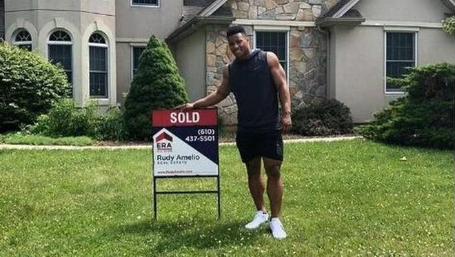 Saquon Barkley stands in front of the house he bought for his parents.