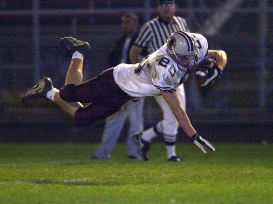 Menomonee Falls' Brett Hirsch dives into the end zone to give them an early 7-0 lead over Marquette University High School at Hart Park on October 18, 2000.