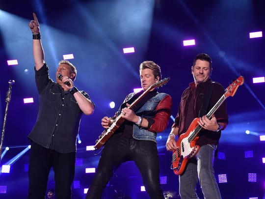 Gary LeVox, Joe Don Rooney and Jay DeMarcus of Rascal Flatts perform onstage at the 2014 CMA Festival on June 5, 2014, in Nashville.