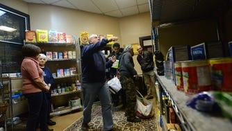 The Rev. Jim Petroccione, center, and volunteers at work at the food pantry at The Church of the Holy Communion in Norwood.