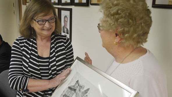 Eileen Morris, left, accepts a framed print of Fanwood's historic north side train station from Council President Kathy Mitchell after being named as the borough's volunteer of the month at a borough council meeting in Fanwood, on March 21. Morris is the longtime leader of the group that oversees and maintains the many floral planters in the borough's downtown area.