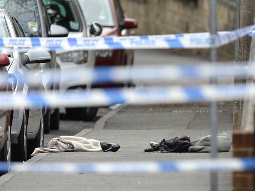 Police crime scene tape surrounds a shoe and handbag