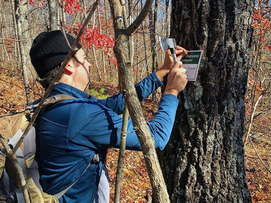 JK McKight hangs preserve boundary signs on Pine Mountain.
