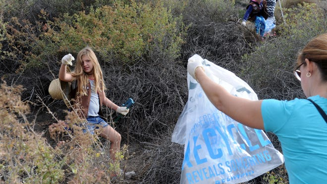 Sloane Briggs, left, with Girl Scout Troop 1656 in Agoura Hills calls Charlene Andrews to bring over the trash bag during Coastal Cleanup Day efforts Saturday near Mugu Rock.