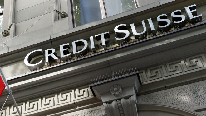 An Aug. 1, 2014 file photo shows the logo of Swiss bank Credit Suisse and a Swiss flag in Zurich, Switzerland.