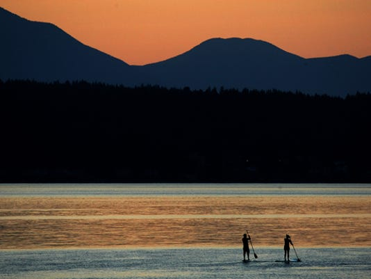 A pair of stand up paddleboarders head into Dyes Inlet as the sun goes down. (LARRY STEAGALL / KITSAP SUN)