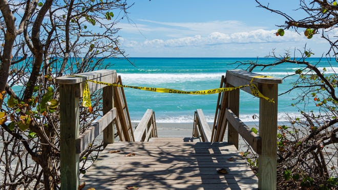 One of the many cordoned off entryways to the beach in Jupiter. The town' sbeaches are closed due to the coronavirus pandemic.