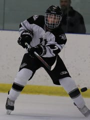 Clearing the puck out of danger for Plymouth is senior defenseman Zack Wiener.