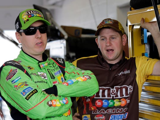 Kyle Busch, left, talks to a crew member in the garage area before the NASCAR Sprint Cup Series practice auto race, Saturday, Nov. 21, 2015, at Homestead-Miami Speedway in Homestead, Fla. (AP Photo/Terry Renna)
