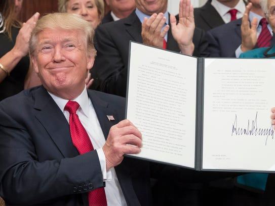 US President Donald J. Trump holds up an executive