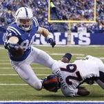 Indianapolis Colts' Jack Doyle (84) dives for a three-yard touchdown reception while being tackled by Denver Broncos' Darian Stewart (26) during the first half of an NFL football game, Sunday Indianapolis.