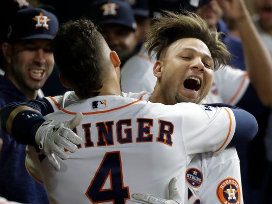 Houston Astros' Yuli Gurriel is congratulated by George Springer after hitting a home run during the second inning of Game 3 of baseball's World Series against the Los Angeles Dodgers Friday, Oct. 27, 2017, in Houston. (AP Photo/David J. Phillip)