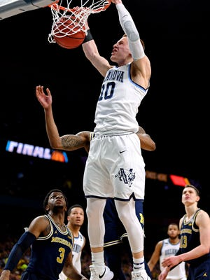 Villanova Wildcats guard Donte DiVincenzo (10) dunks the ball against Michigan Wolverines guard Charles Matthews (1) during the first half in the championship game of the 2018 men's Final Four at Alamodome.