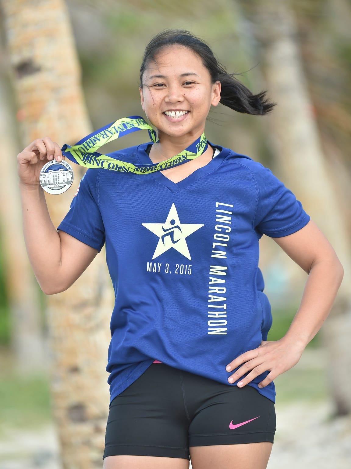 Sheryl May Padilla, a Guam National Guard soldier from Yigo, shows a recent marathon medal at Asan Beach Park on April 7. Padilla has qualified for the upcoming Boston Marathon.