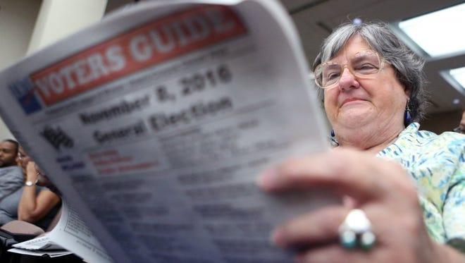 Cynthia Herin reviews a voter guide before a League of Women Voters-Corpus Christi candidate forum Thursday, Oct. 13, 2016, at Corpus Christi City Hall.