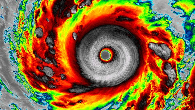 A colorized satellite photo shows Super Typhoon Vongfong spinning in the western Pacific Ocean.